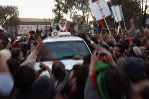 Former Prime Minister Benazir Bhutto waves from her car just seconds before being attacked on Decemb