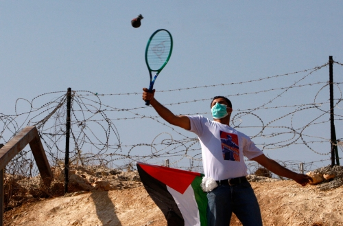 photo: A Palestinian demonstrator uses a tennis racket to return an empty tear gas canister