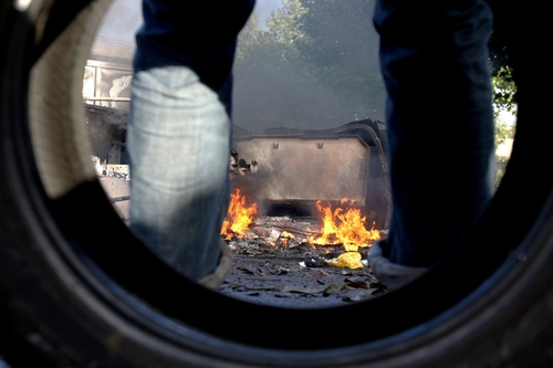 France, Caen, 19 October 2010: Protesters based on the tire and looking at the Burning Car. AFP PHOT