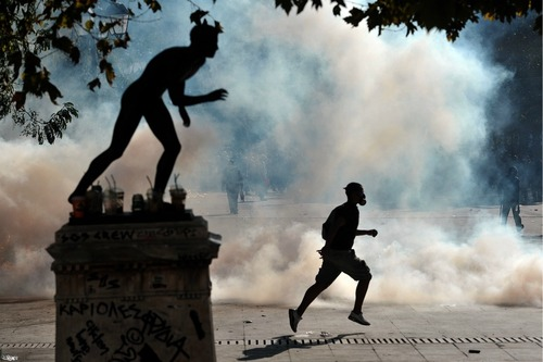 A demonstrator runs away from tear gas in Athens on Oct. 20