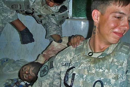 A soldier from the Army's 82nd Airborne Division with a dead insurgent's hand on his shoulder.