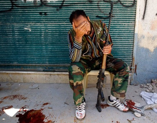A Free Syrian Army fighter reacts after his friend was shot by Syrian Army soldiers during clashes i