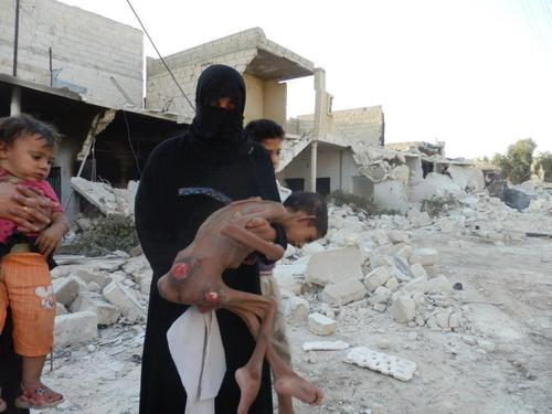 #Hama, #Syria: A mother carries her child