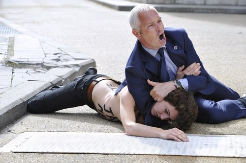 A security guard tackles a Femen activist...