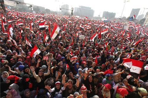 Protesters against Egyptian President Mohamed Mursi wave national flags in Tahrir Square in Cairo, J