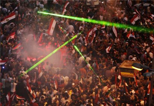 Laser lights are flashed as protesters against Egyptian President Mohamed Mursi gather in Tahrir Squ