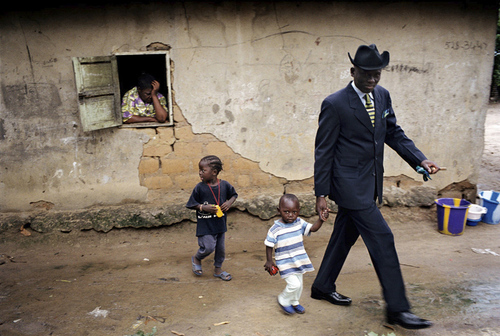 The sapeur Willy Covari, one of the most admired sapeurs of the Bacongo neighborhood, walks with his