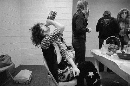 Jimmy Page drinking whiskey while other Led Zeppelin members eat and smoke before a concert.