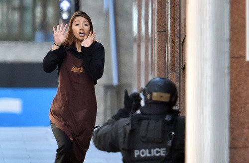 One of the hostages runs towards police from a cafe in the central business district of Sydney on De