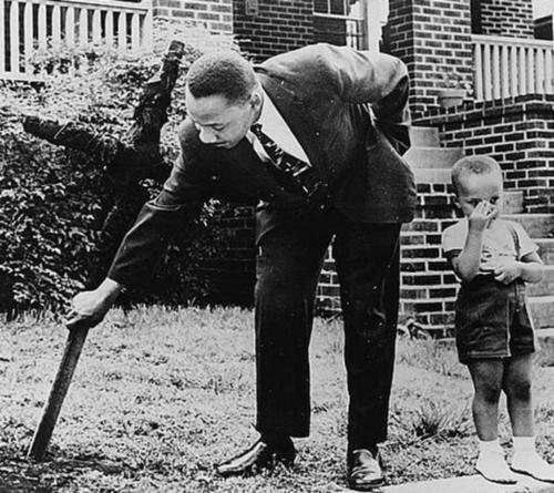 Martin Luther King jr. removing a burning cross from his yard. The child beside him is his son