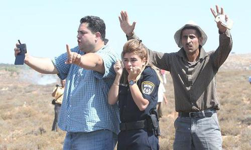 Terrified Israeli policewoman protected by Palestinians while pelted by rocks from settlers. (Pictur