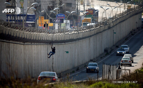 A Palestinian man uses a rope to climb over a...